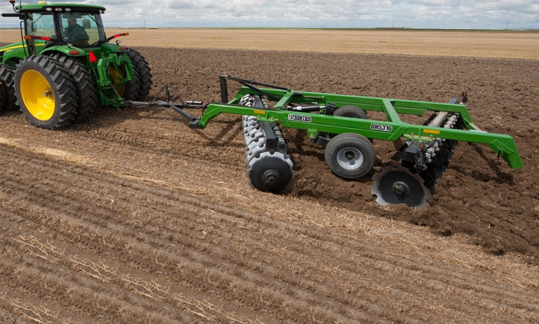 John Deere tractor using Drawn Offset Disks to plow a field