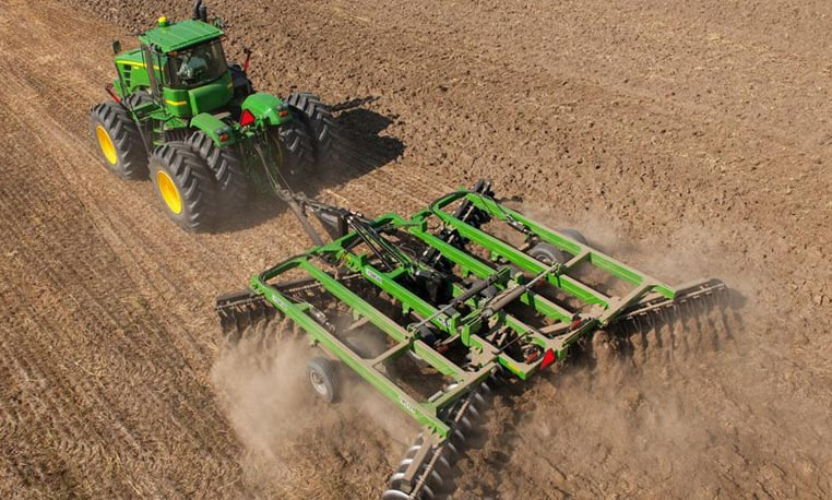 Overhead view of a John Deere tractor with tillage equipment working in a field