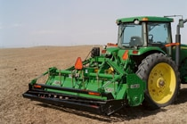 Rear view of a John Deere tractor using a RC13 Series Row-Crop Rotary Tiller to plow a field