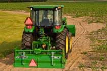 Rear view of a John Deere tractor with RT22 Series Rotary Tiller working in a field