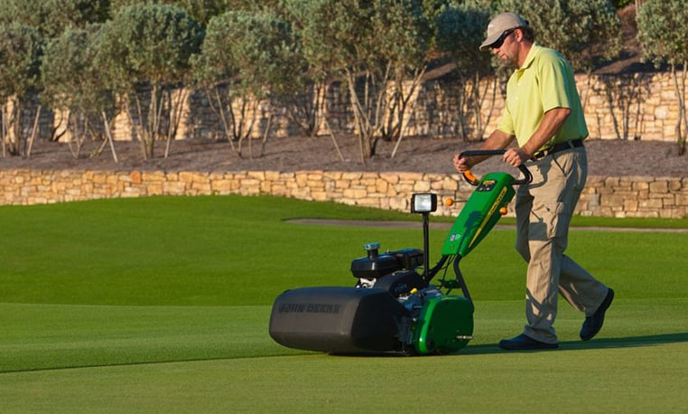 Worker operates an SL PrecisionCut Walk Greens Mower on a golf course