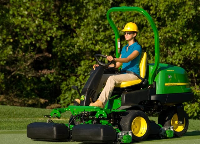 Worker uses 2500E E-Cut Hybrid Gas mower to mow golf course green
