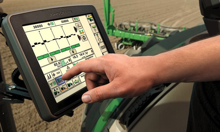 Closeup of a display in a John Deere tractor with a freshly plowed field in the background