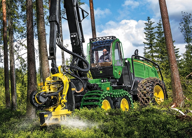 Front three quarter view of the 1270G Wheel Harvester sawing into a tree in the forest