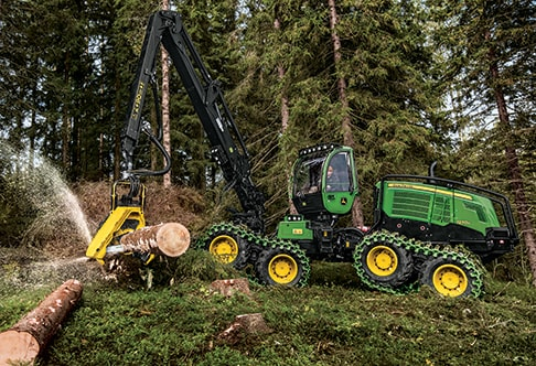 Ground-level view of the 1270G 8W Wheeled Harvester cutting into a log at a job site
