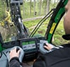 Looking out the 1270G 8W Wheeled Harvester cab window from the point of view of the operator