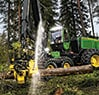 Front three quarter view of the 1470G Wheeled Harvester sawing fallen log at a job site
