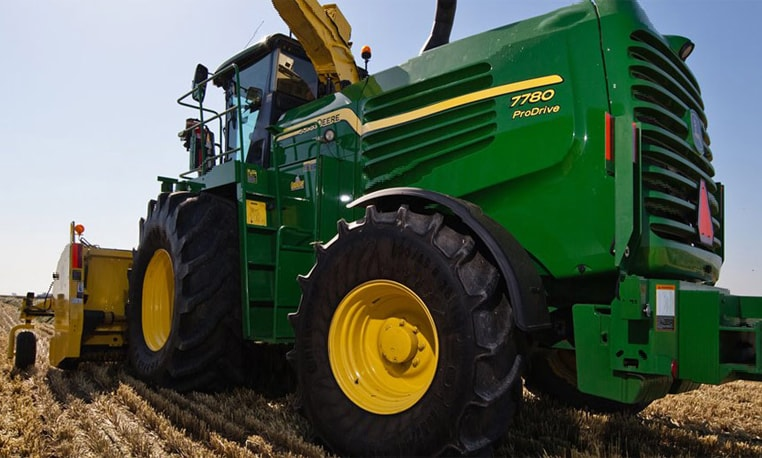 Ground-level view of a 7080 Series Self-Propelled Forage Harvester working in a field