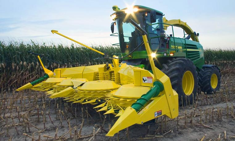 John Deere Forage Harvester with SPFH Corn Header working in a field at dusk