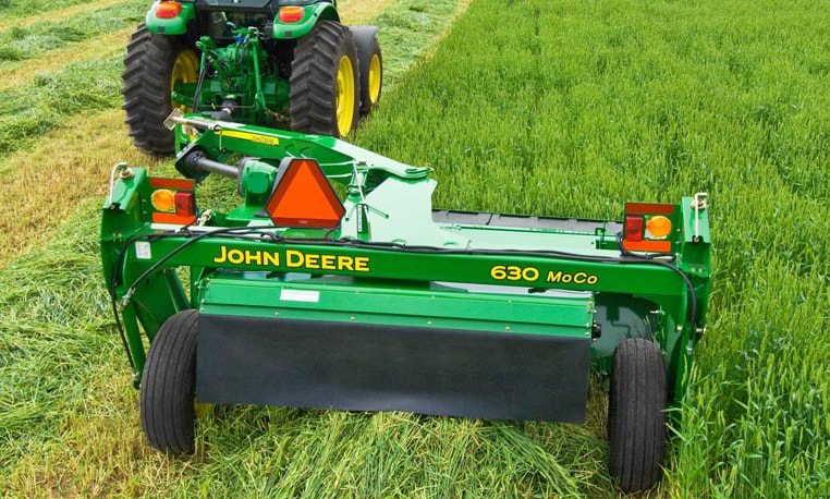 John Deere tractor using a 600 Series Mower-Conditioner in a field