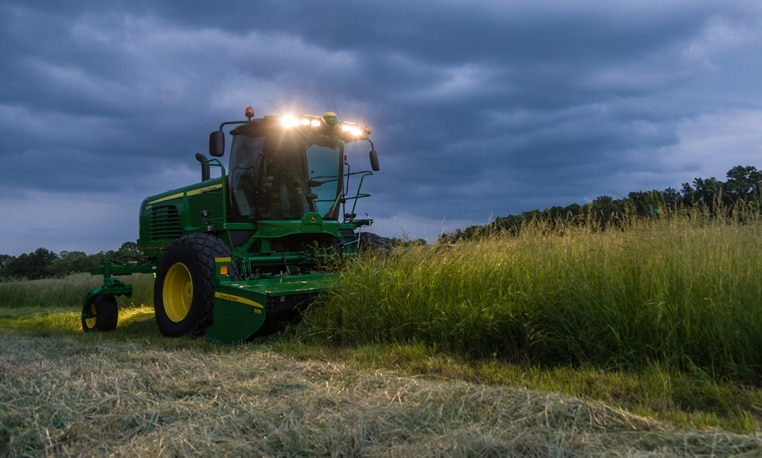 John Deere Windrower in a field at night