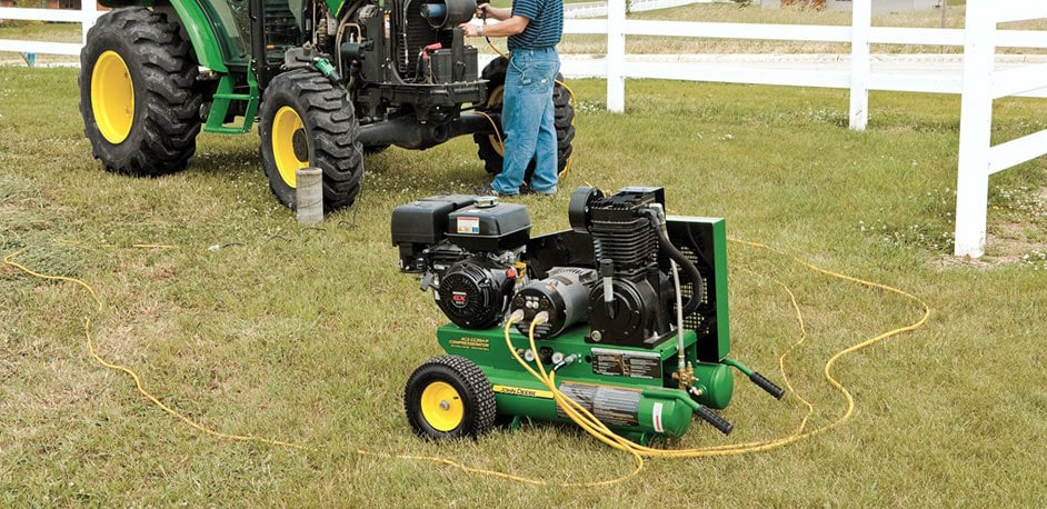 John Deere Compresserator on a lawn with a man fixing a tractor in the background