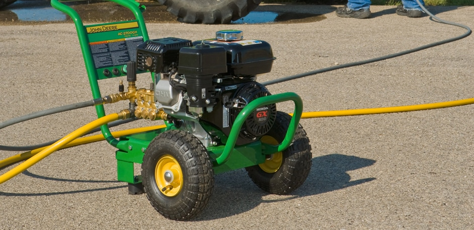 Closeup of a John Deere Pressure Washer on a driveway with a tractor in the background