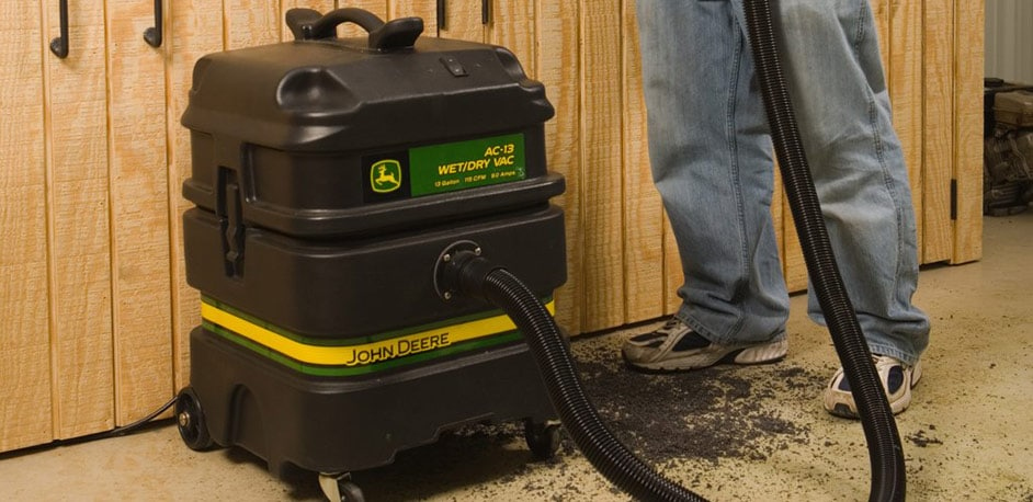 man using a John Deere wet/dry vacuum in a garage