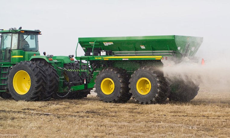 Drawn dry spreader being pulled by a John Deere tractor in a dusty field