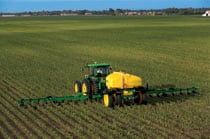 John Deere tractor using the 2510L Liquid Fertilizer Applicator in a field with blue sky in the background