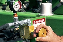 Closeup of a man's hand turning a knob to adjust the box drill's down pressure