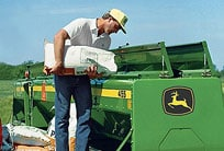 Farmer emptying a bag of seed into a drill box