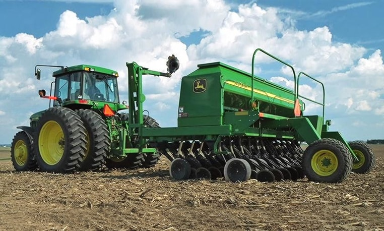 John Deere tractor with a Box Drill attachment in a harvested corn field