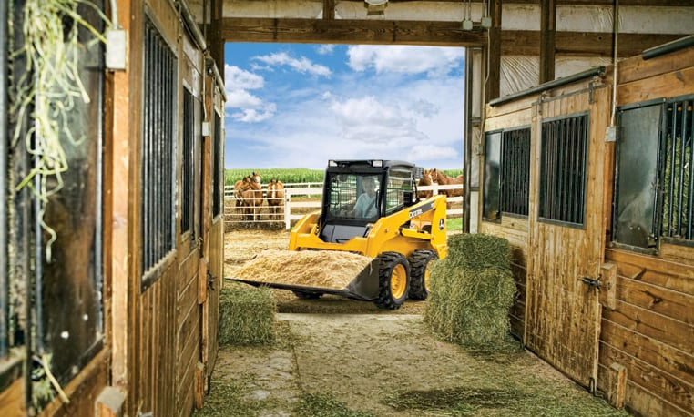 Skid steer with straw in bucket heading into a barn