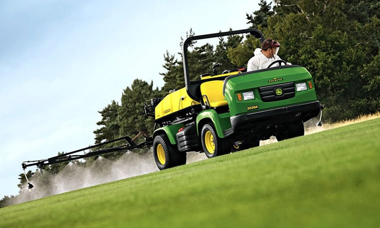 A worker uses a John Deere sprayer to treat turf