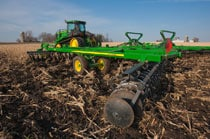 Closeup of the tillage equipment attached to a John Deere tractor working in a field