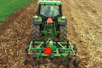 Rear view of a John Deere tractor with 714 Mulch Tiller in a field