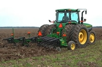 Side view of a John Deere tractor with 915 V-Ripper working in a field