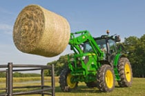 6R Series Tractor with hay bale