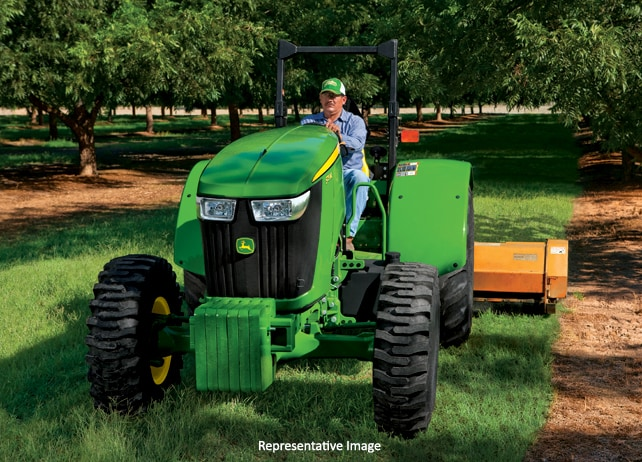 Man using a 5115ML Tractor with mowing attachment to trim grass