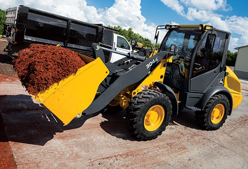 304K Compact Loader with bucket full of landscaping mulch