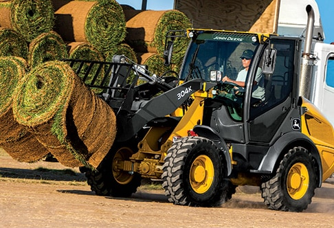 304K Compact Loader with fork attachment moving two rolls of grass sod