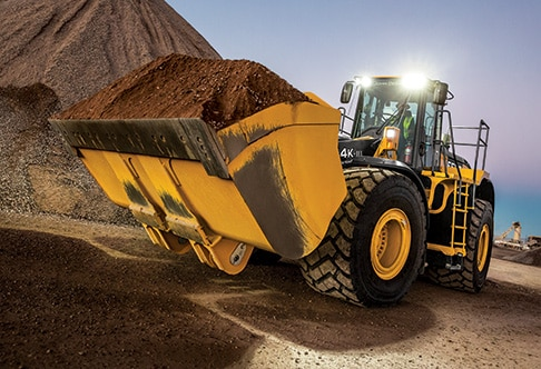 Front three quarter view of 844K-III Aggregate Handler Wheel Loader traveling with full bucket of processed gravel