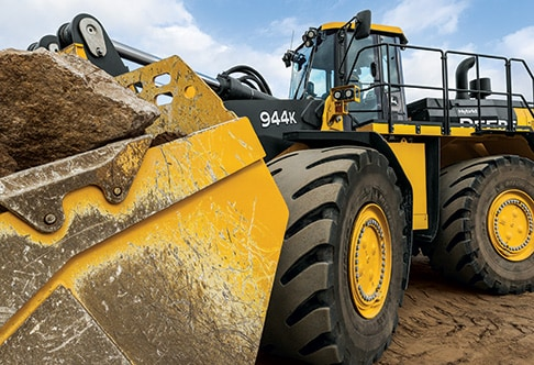 Close up view of the 944K Hybrid Wheel Loader with a large rock in the bucket