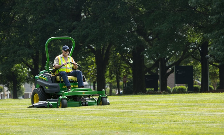 Landscape worker using a ZTrak Z997R Diesel Series mower to trim the lawn.