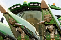 Closeup of a corn header on a combine as it harvests corn in a field