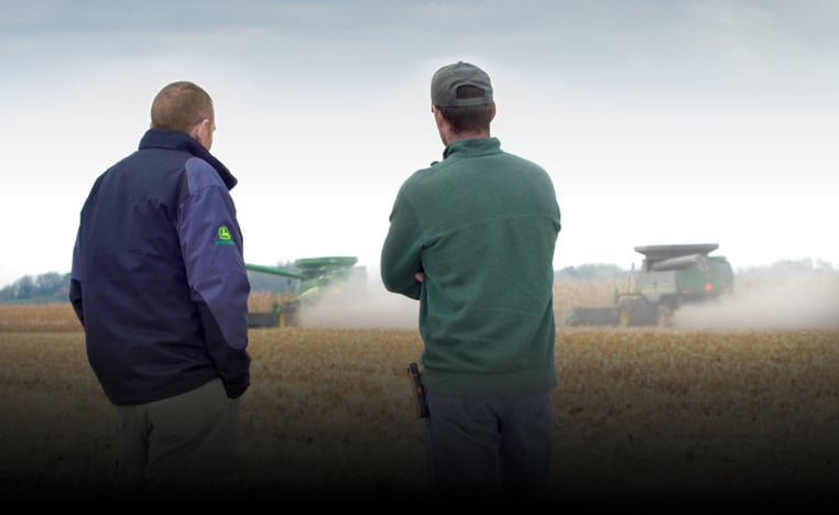 two guys watching combines in the field