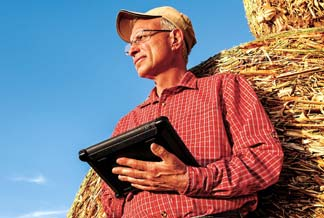 Farmer with hay bales and iPad