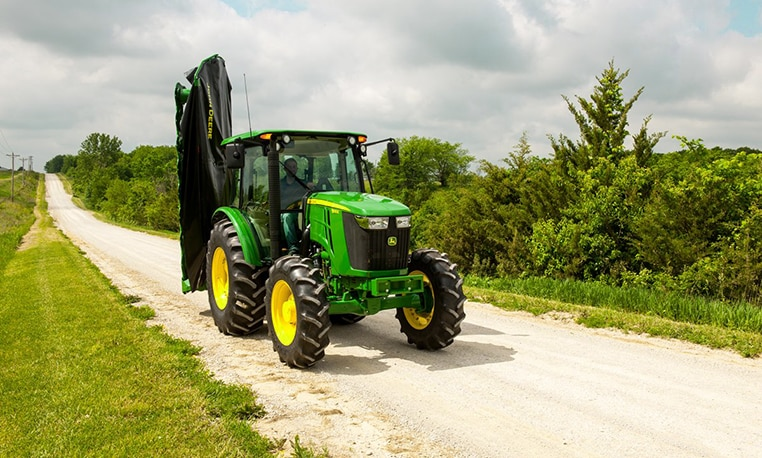 Image of disc mower on tractor in field pathway