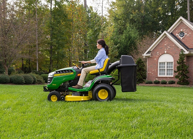 Woman riding D130 lawn tractor edging a garden bed