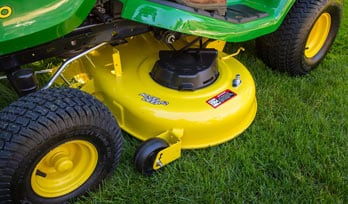 Close up image of the mower deck moving through grass
