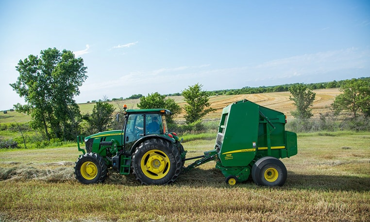 6E Series Utility Tractor with baler in field
