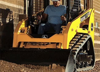 Man operates skid steer with dirt bucket