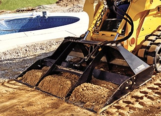 Skid steer with landplane attachment leveling soil next to a new inground pool