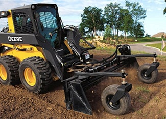 Skid Steer using power rake attachment at a job site