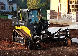 Skid Steer using power rake attachment at a residential job site
