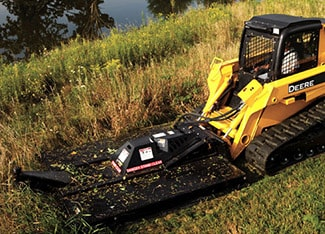 Skid Steer using rotary cutter attachment to trim grass near a pond