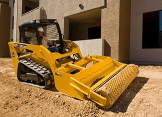 Skid Steer using roller level attachment to level soil at a job site