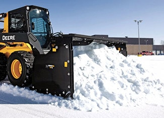 Skid Steer with Snow Pusher attachment clearing snow in a parking lot