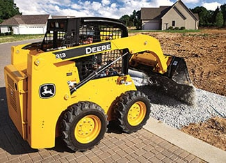 Skid steer uses a utility bucket to unload gravel